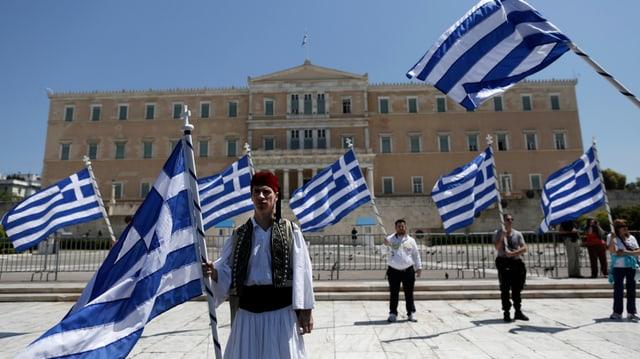Vor dem griechischen Parlament stehen protestierende Gemeindearbeiter mit Griechen-Flaggen.