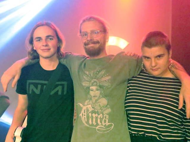 Zwei Musiker und eine Musikerin posieren für die Kamera.