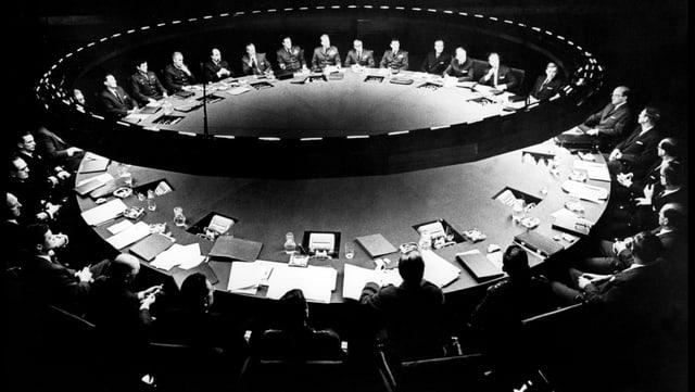 Ein riesiger Konferenztisch an dem Männer sitzen.