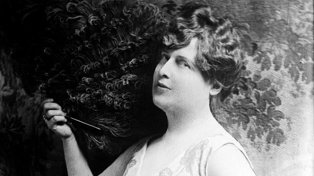 Eine Frau mit Hocksteckfrisur und Fächer schaut lasziv in die Kamera.