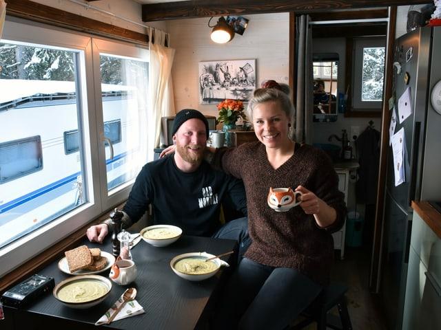 Mann und Frau posieren an einem Tisch mit drei Tellern Suppe.