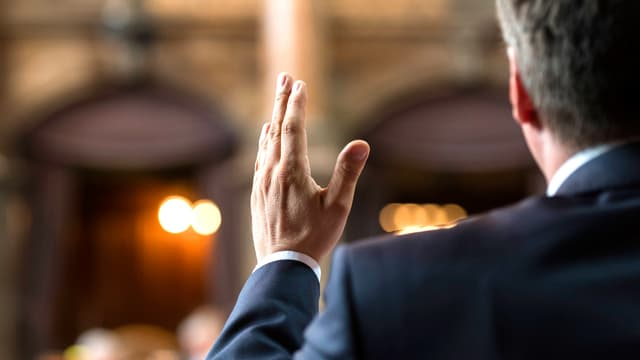 Parlamentarier von hinten. Seine Hand schneidet den Plenarsaal in zwei Hälften.