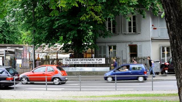 Strasse mit Autos, Gebäude im Hintergrund, Plakat mit «Tag der offenen Tür»