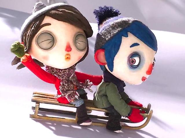 Filmheld Courgette rast mit seiner Freundin auf dem Schlitten den Schneehang hinab.