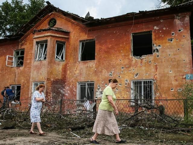 Frauen spazieren an einem durchlöcherten Haus vorbei