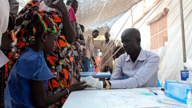 Ein Mädchen wird von einem Arzt auf Malaria untersucht.