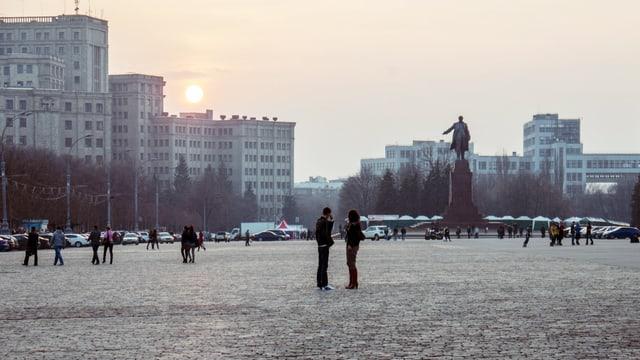 Ein Platz mit einer Leninstatue, im Hintergrund Hochhäuser.
