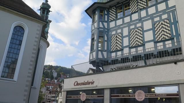 Chocolaterie, darüber eine Terasse mit Geländer, umgeben von zwei Häusern.