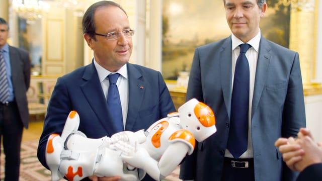 François Hollande hält einen Roboter im Arm.