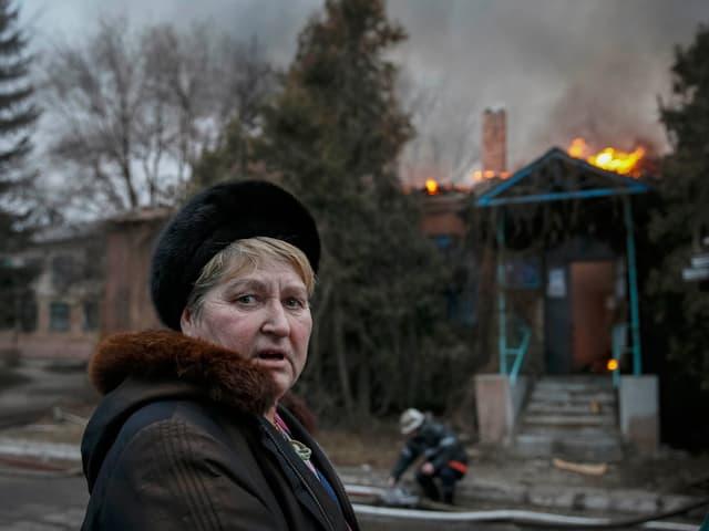 Eine Frau blickt in die Kamera, hinter ihr ein brennendes Haus.