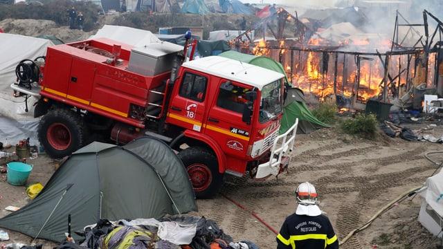 Feuerwehrwagen neben brennendem Gerüst