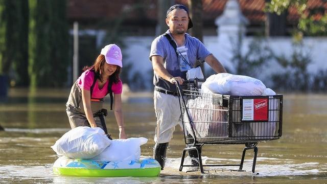 Paar schiebt Einkaufswagen durch das Wasser.