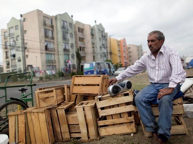 Mann sitzt in Chile auf Harrassen und hört Radio.