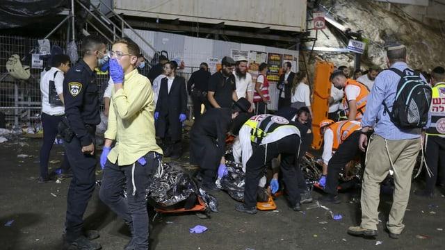 Equipes de resgate removem os mortos após um pânico em massa.