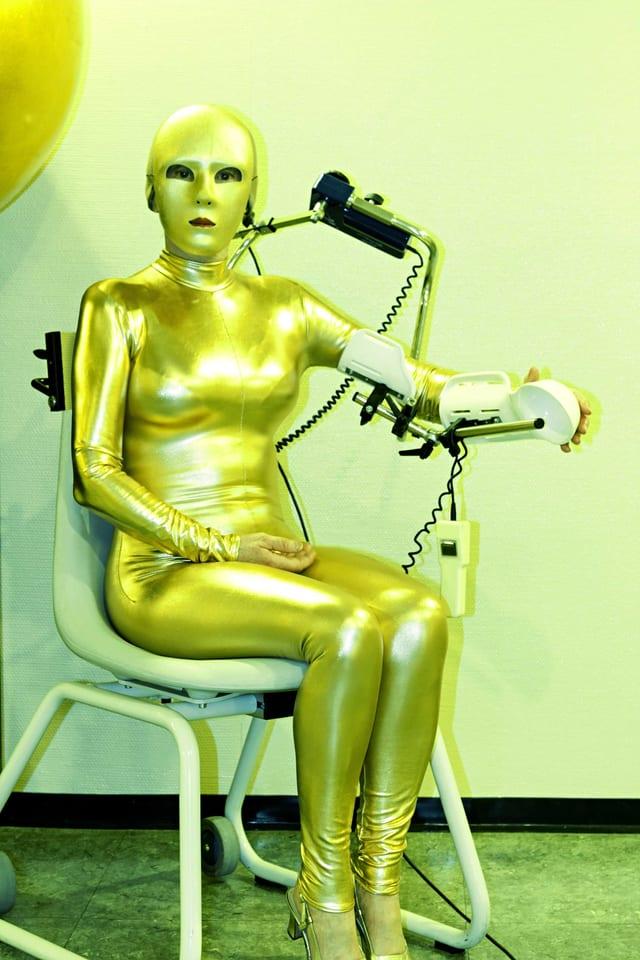 Eine Frau sitzt im goldenen Latex-Overall auf einem Stuhl.