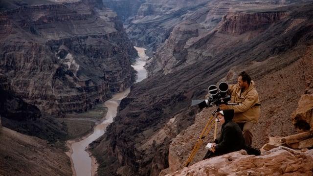ein Mann steht mit der Kamera in den Bergen