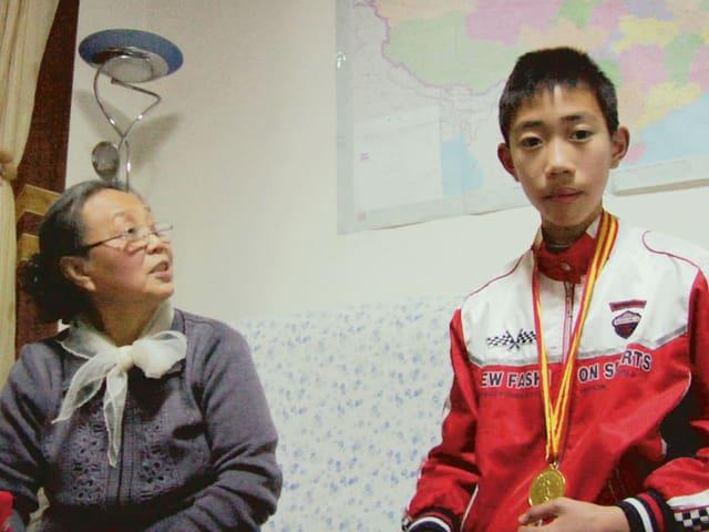 Ein chinesischer Schüler mit Goldmedaille um den Hals, daneben seine Grossmutter.