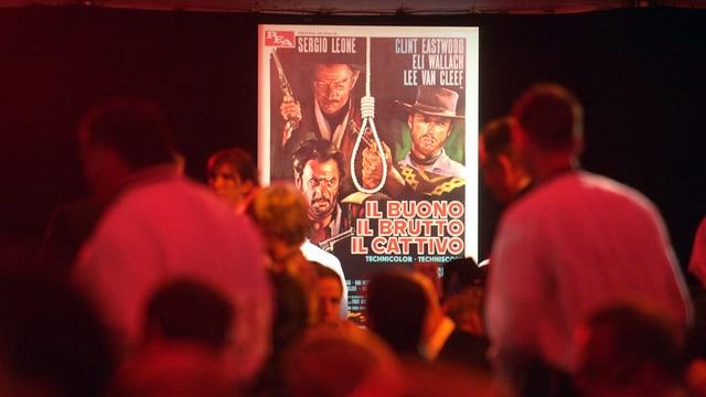 Menschen betrachten das Filmplakat von «Il Buono, Il Brutto, Il Cattivo».