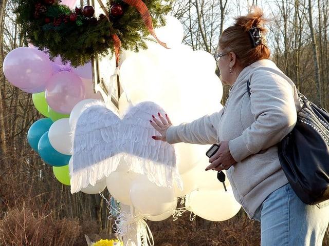 Eine Frau berührt ein paar Engelsflügel, dahinter schweben weisse Luftballons.