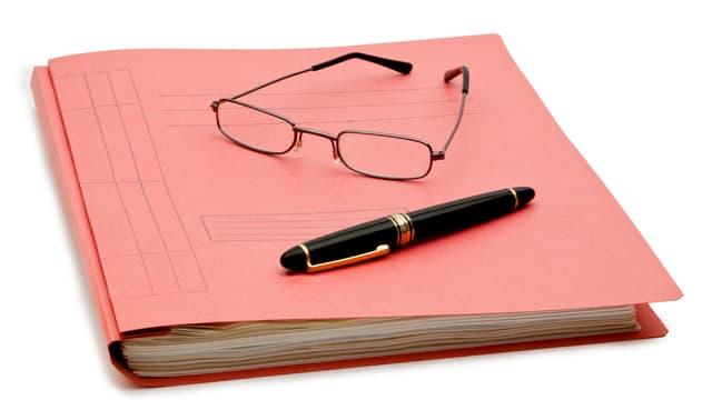 Ein kleiner Ordner, darauf eine Brille und ein Kugelschreiber.
