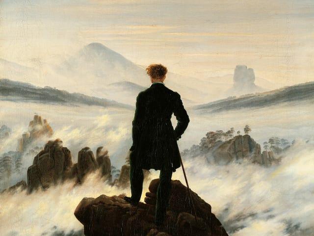 Bild eines Mannes, der auf einem Felsen steht und auf ein Nebelmeer schaut.