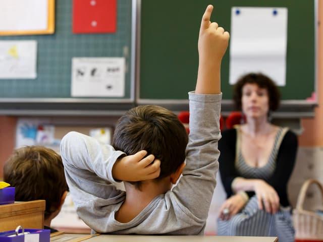 Schüler streckt den Finger, Lehrerin im Hintergrund.