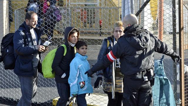 Eine Flüchtlingsfamilie mit zwei Kindern geht über die Grenze in Österreich.