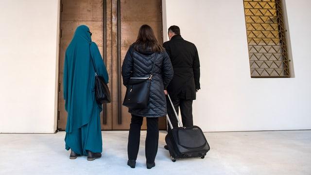 Drei Personen vor einer Tür.