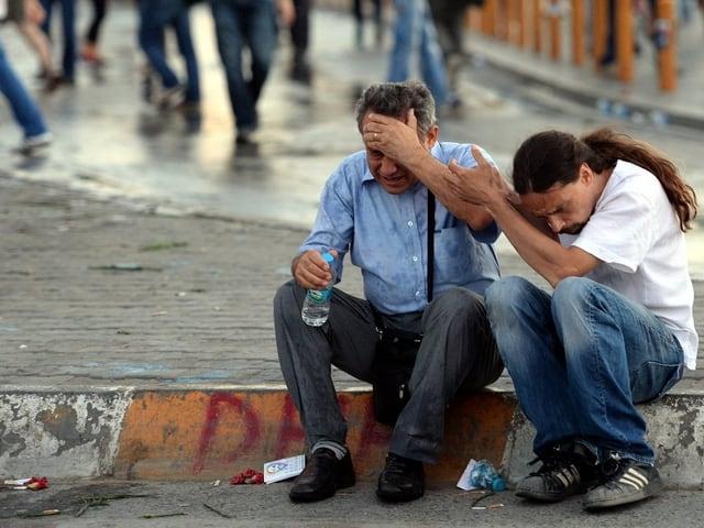 Zwei Männer abseits der grossen Demonstrationen, einer von ihnen verletzt
