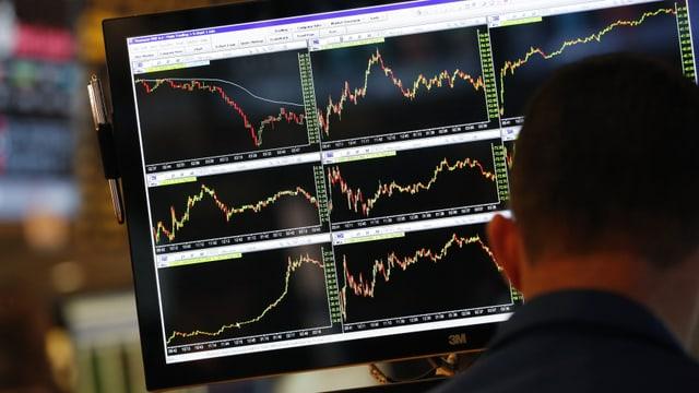 Ein Händler sitzt vor einem Bildschirm, auf dem die Aktienkurse abgebildet sind.