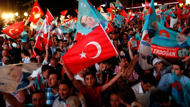Menschen schwenken Türkei- und Erdoganfahnen.