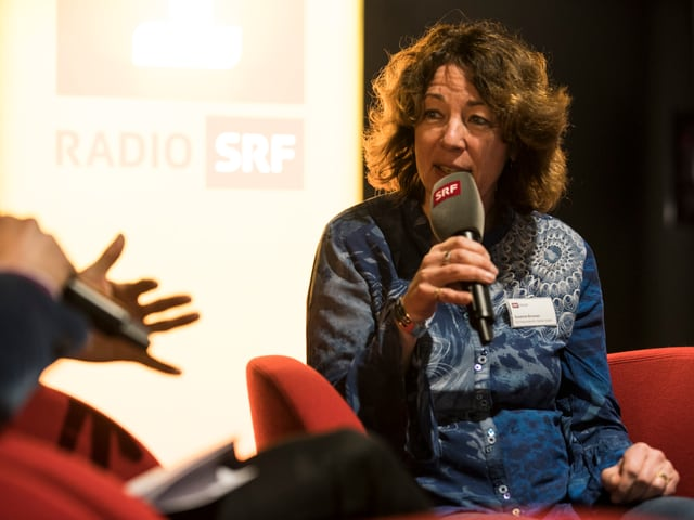 Frau in rotem Sessel mit Mikrofon in der Hand