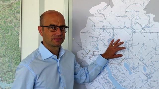 Ein Mann steht vor einer Karte des Kantons Zürich mit Haltestellen.