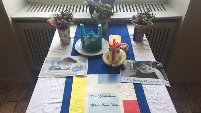 Tisch mit Kerzen, Briefen und Bildern
