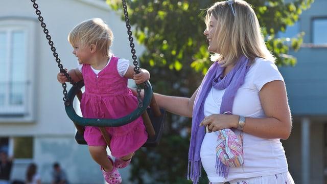 Frau mit ihrem Kind auf dem Spielplatz.