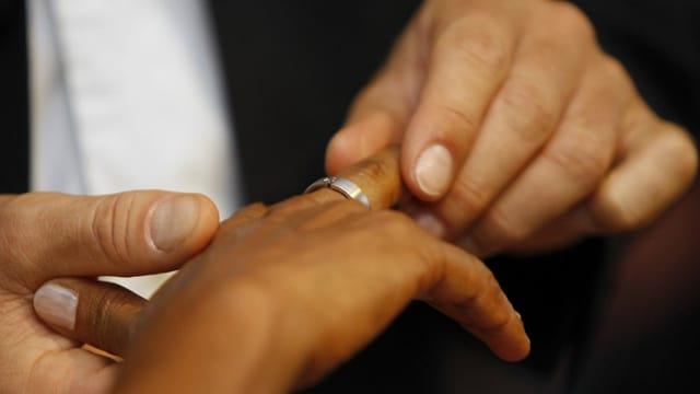 Ein heller Mann steckt einer dunklen Frau einen Ring an den Finger.