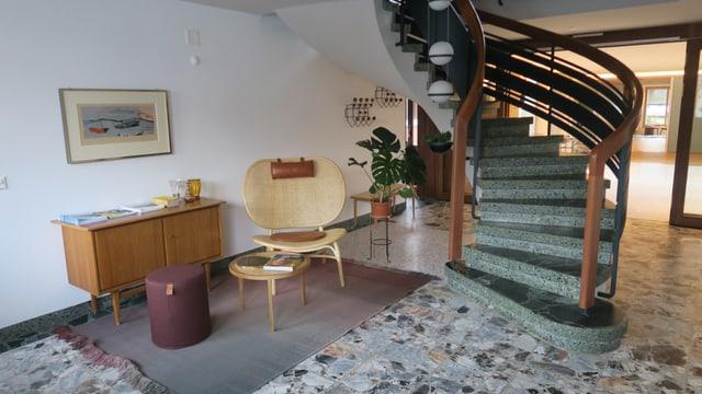 Eine Treppe führt von einem Raum mit Sitzbereich in den oberen Stock.