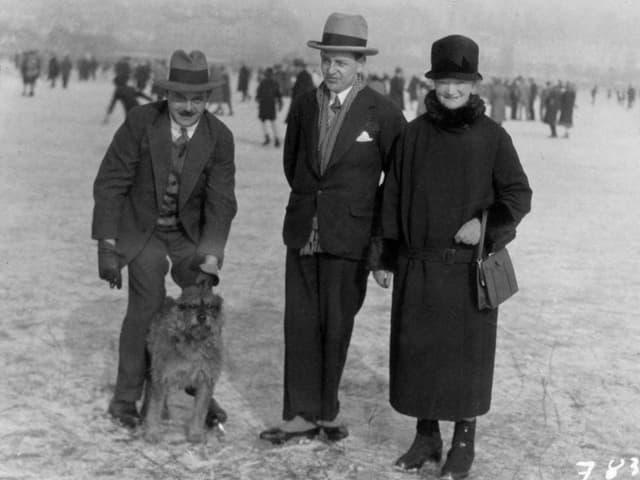 Zwei Männer, eine Frau und ein Hund auf einem gefrorenen See.