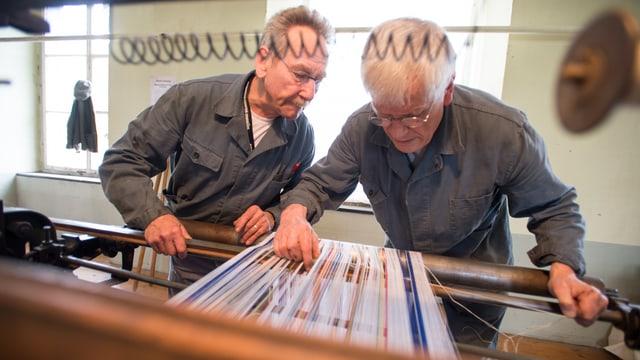 Die beiden Webmeister Hans Hiestand und Walter Koch am Webstuhl