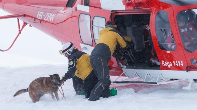 Zwei Retter und ein Lawinenhund vor dem Helikopter