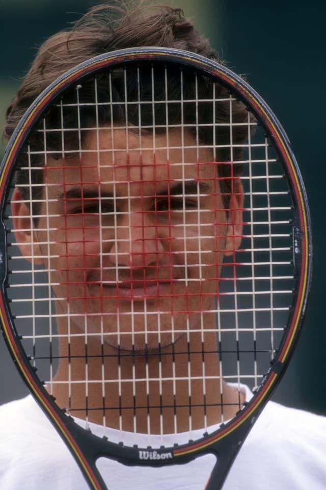Tennisspieler hält Schläger vor den Kopf.