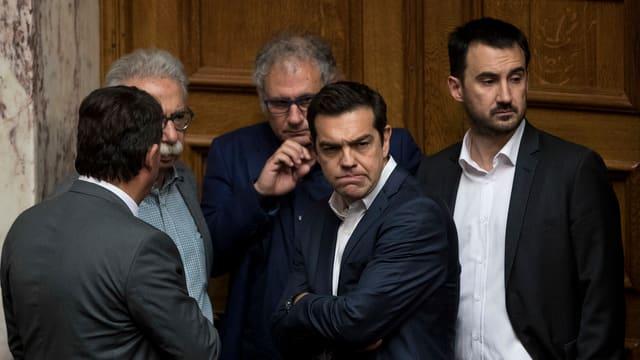 Tsipras steht mit Regierungsmitgliedern im Parlamentsgebäude.