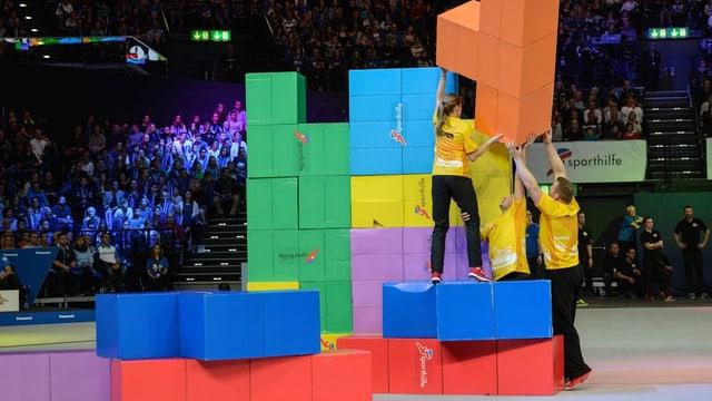 Trais atlets en T-Shirts mellens emplunan elements da Tetris - davostiers vesan ins il public sin tribuna.