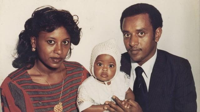 Eine Frau, ein Mann und ein Baby im weissen Kleid blicken in die Kamera.
