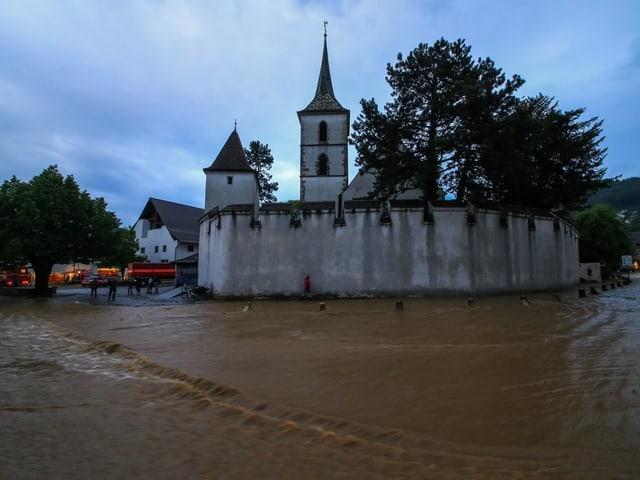 Braunes Wasser am Boden, im Hintergrund eine Kirche