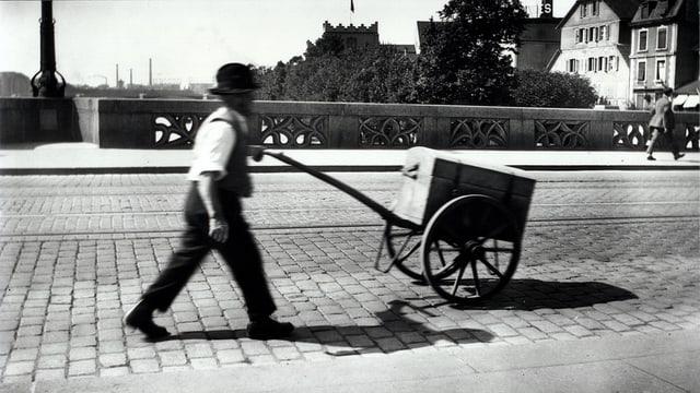 Auf der Schwarz-Weiss-Fotografie schieb ein Mann einen Holzwagen über eine Brücke mit Pflastersteinen.