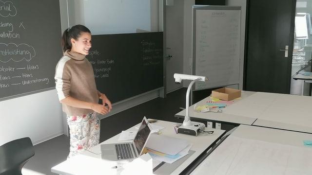 Junge Frau vor Wandtafel und Computer erklärt etwas