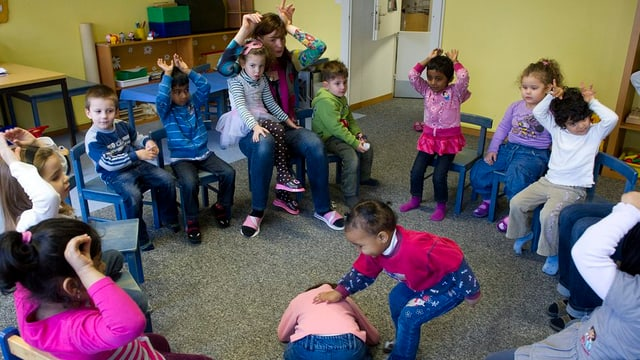 Blick in einen Kindergarten. Die Kinder sitzen im Kreis. Man sieht auch die Kindergärtnerin.