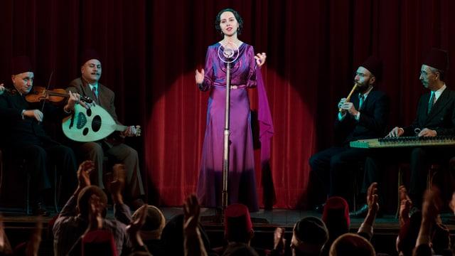 Eine Frau steht auf der Bühne und singt.