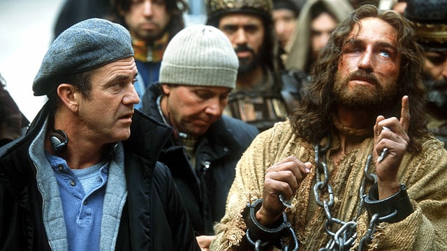 Ein Mann mit Kappe sitzt neben einem Mann, der als Jesus verkleidet ist.